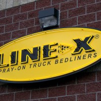 A single faced illuminated fascia sign with yellow neon lettering and boarder.