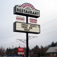 A double faced illuminated fascia sign with illuminated reader board.