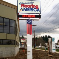 Double faced illuminated freestanding sign with and electronic message center, neon trimming, and an American flag pole cover.